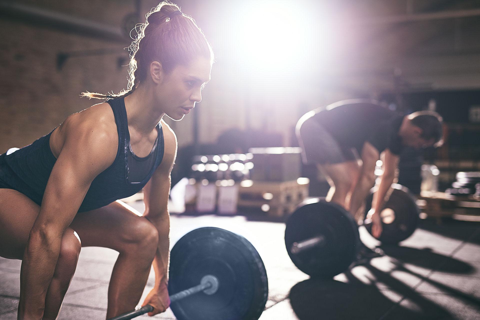 Woman lifting heavy barbells